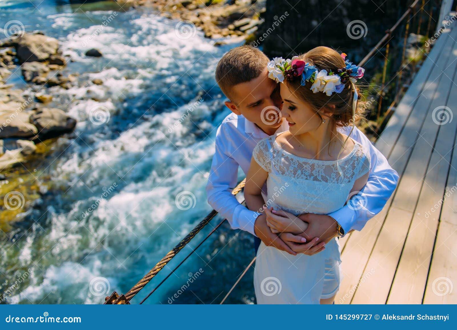 Una coppia di persone appena sposate stanno sul ponte sospeso e sullo sguardo fisso ad a vicenda Nei precedenti, fiume selvaggio
