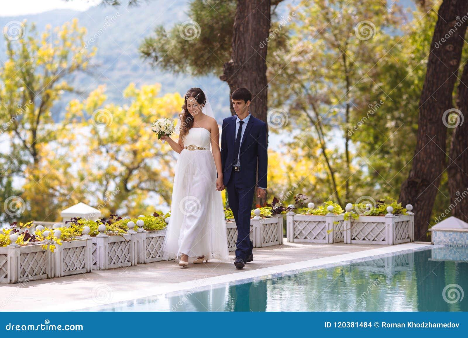 Una coppia felice ha sposato appena la marcia lungo il lungomare che si tiene per mano e che sorride allegramente Lle nozze attes
