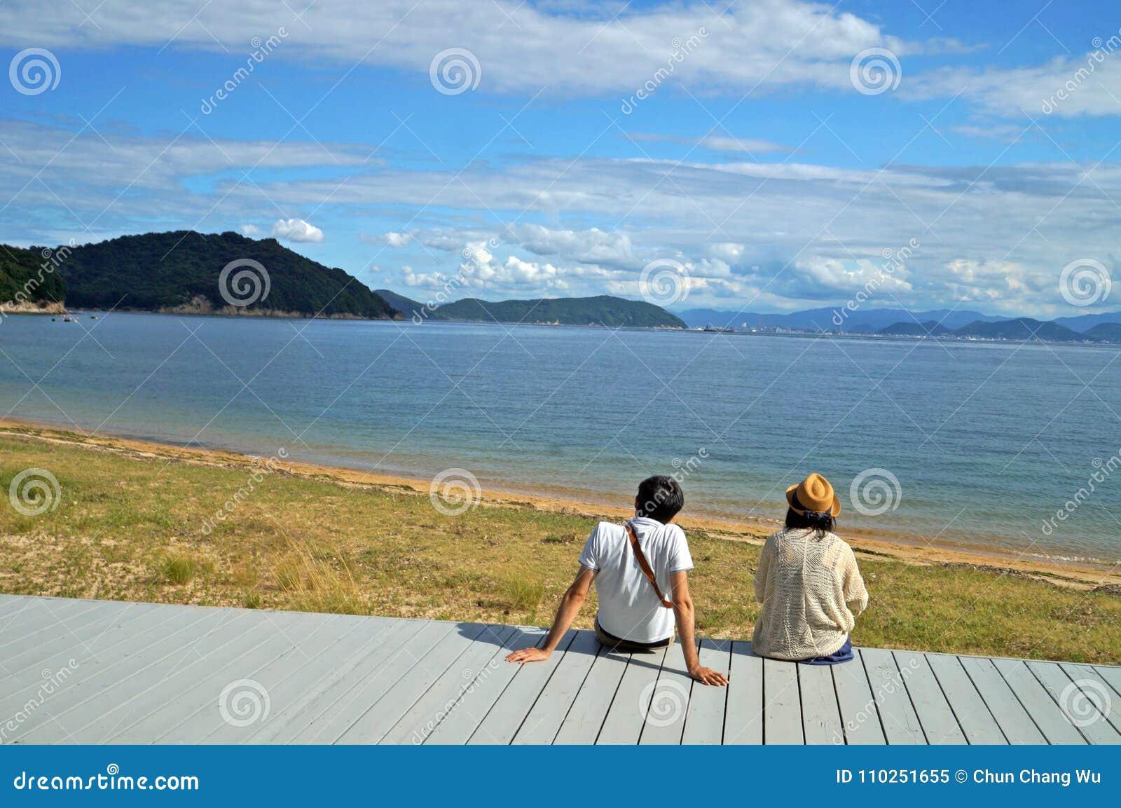 Una coppia si siede sulla piattaforma e gode della vista del mare