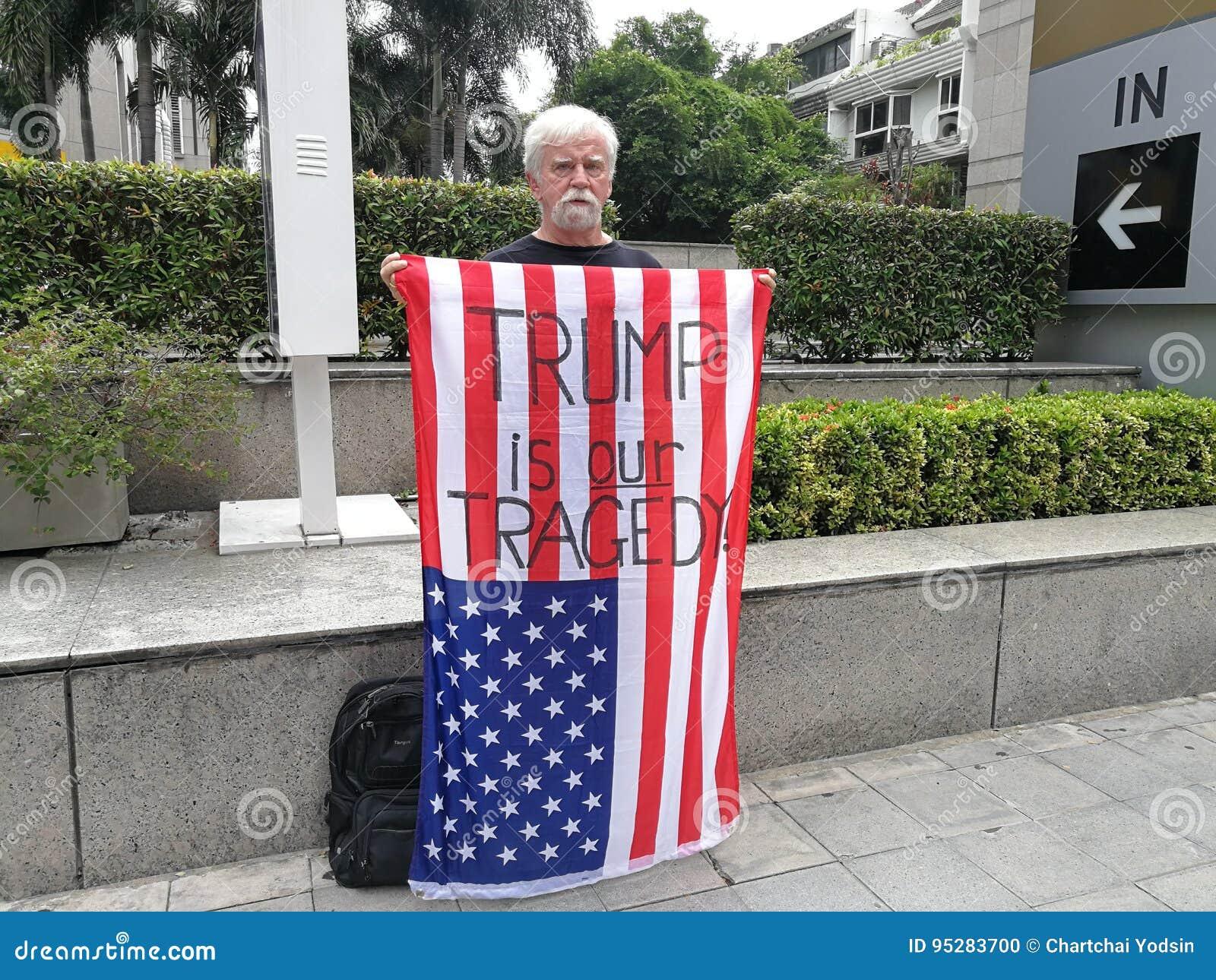 Una demostración americana del hombre la bandera americana con el TRIUNFO del ` de las palabras ES NUESTRA TRAGEDIA ` En el camin