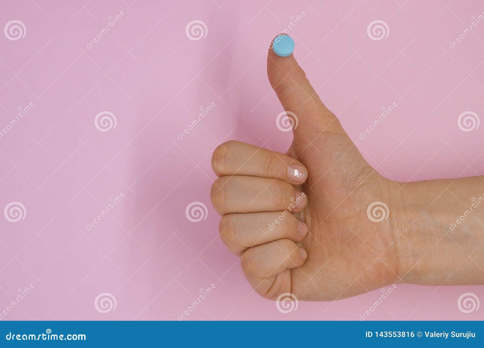 Una demostración de la mano tiene gusto con una píldora médica