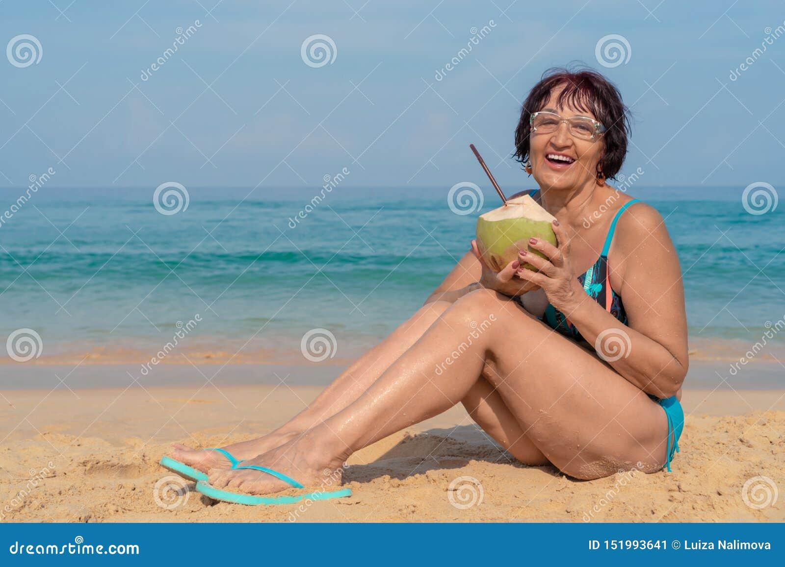Una Donna Anziana Con Capelli Neri Si Siede Dal Mare Un ...