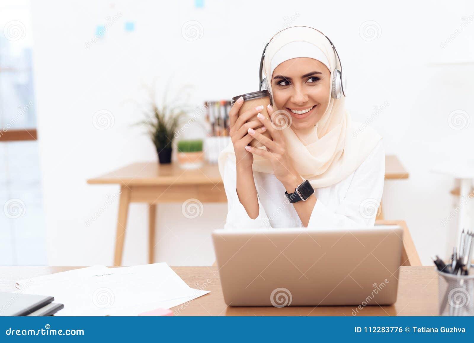 Una donna araba nel hijab ascolta musica sulle cuffie