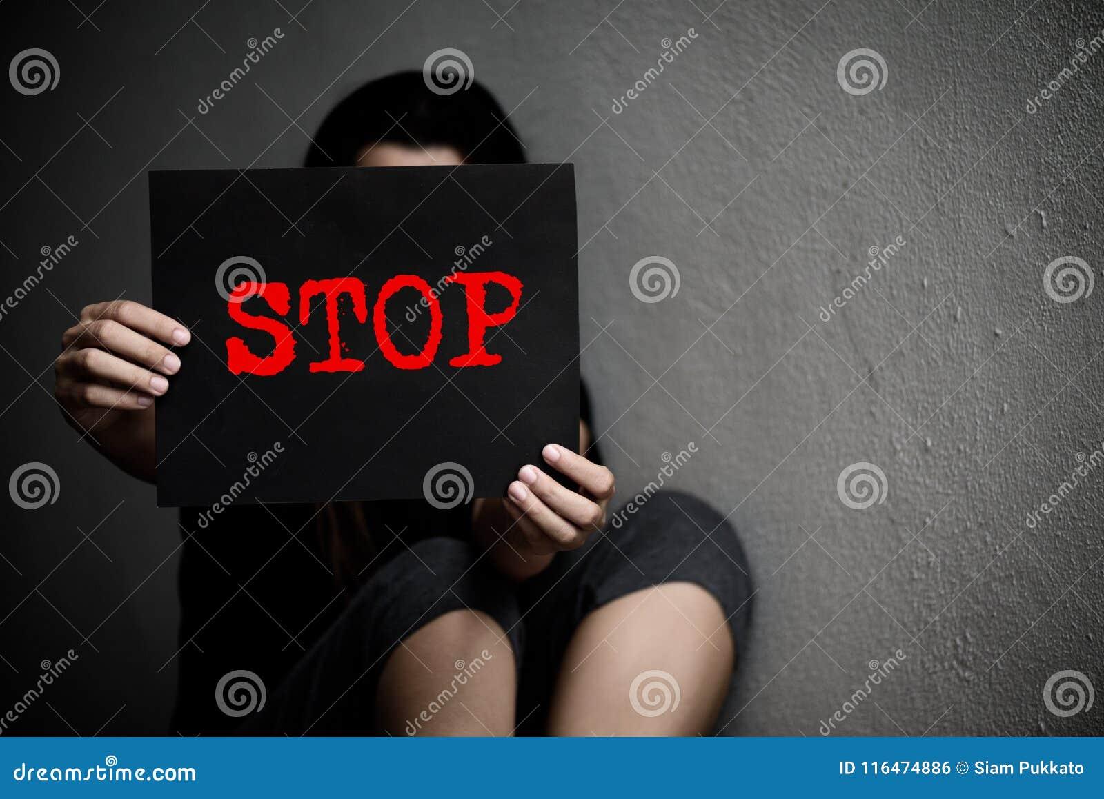 Una donna che tiene un fanale di arresto concettuale sulla violenza contro le donne