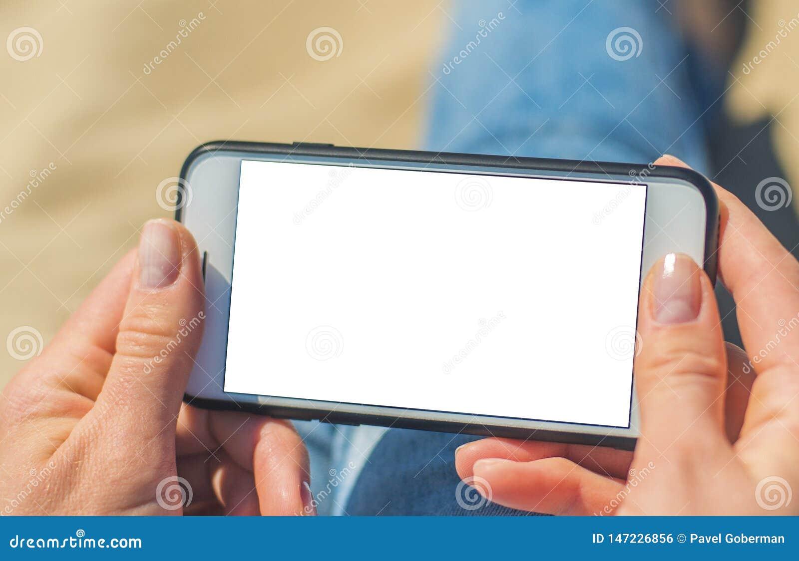 Una donna che tiene un telefono cellulare bianco con uno schermo in bianco