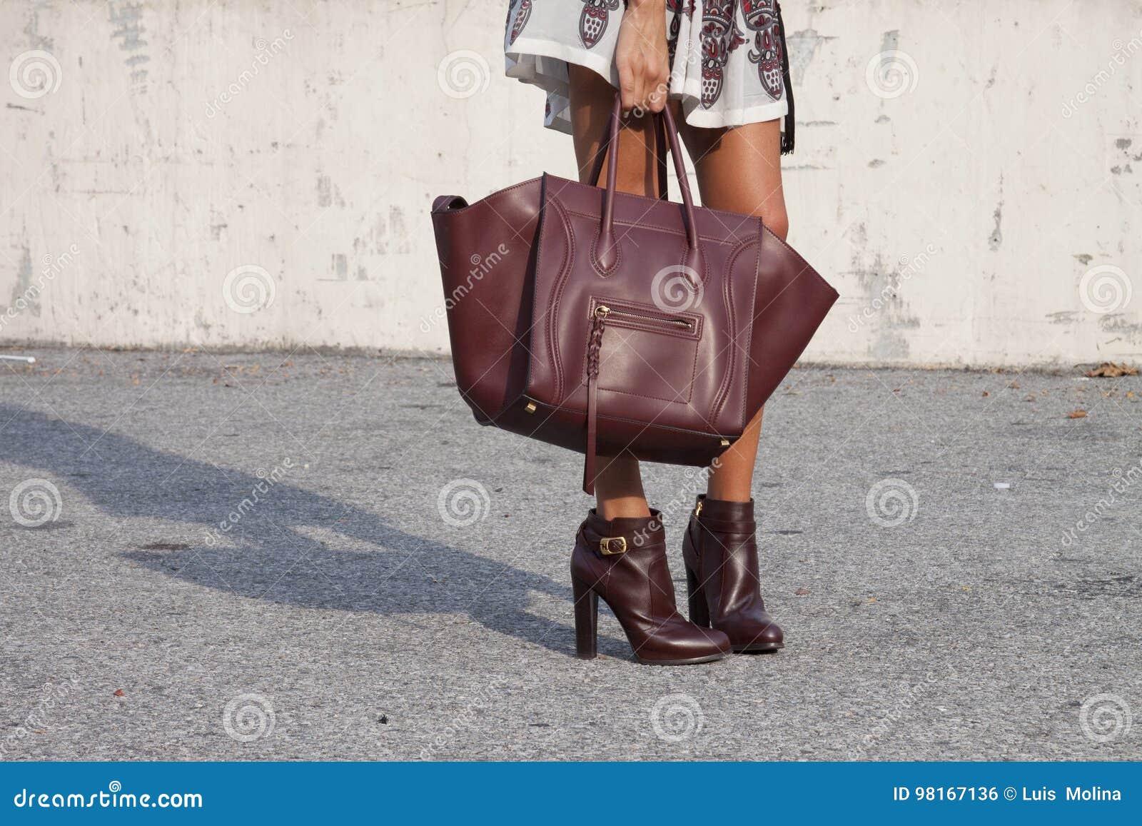 Una donna che tiene una borsa del progettista e che indossa i bottini