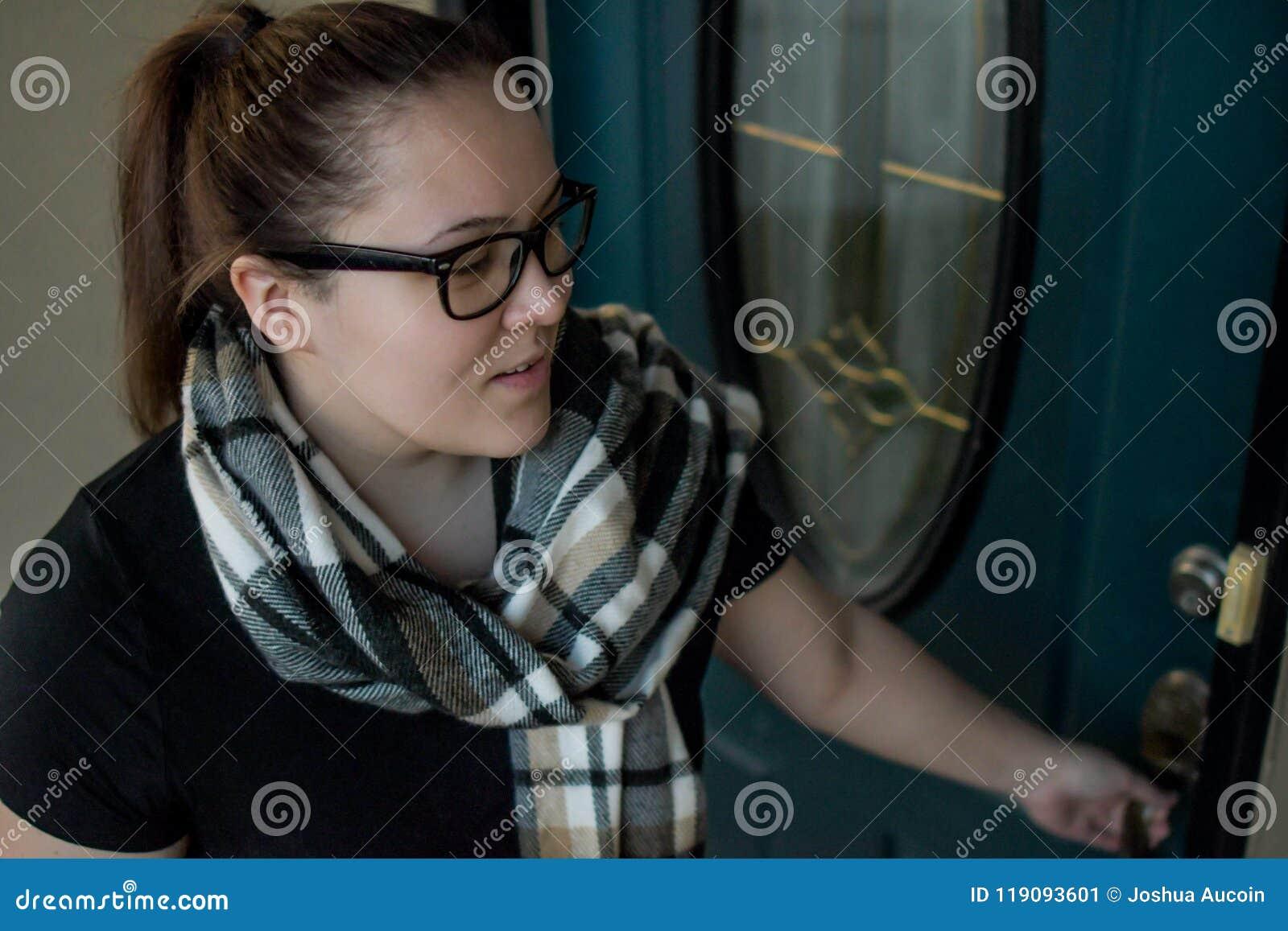 Una donna chiude la sua entrata principale a chiave mentre va via di casa con una borsa di tela oltre un braccio