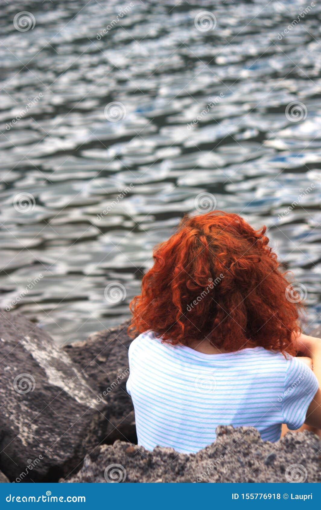 Una Donna Con Capelli Ricci Sta Sedendosi Davanti Al Mare ...