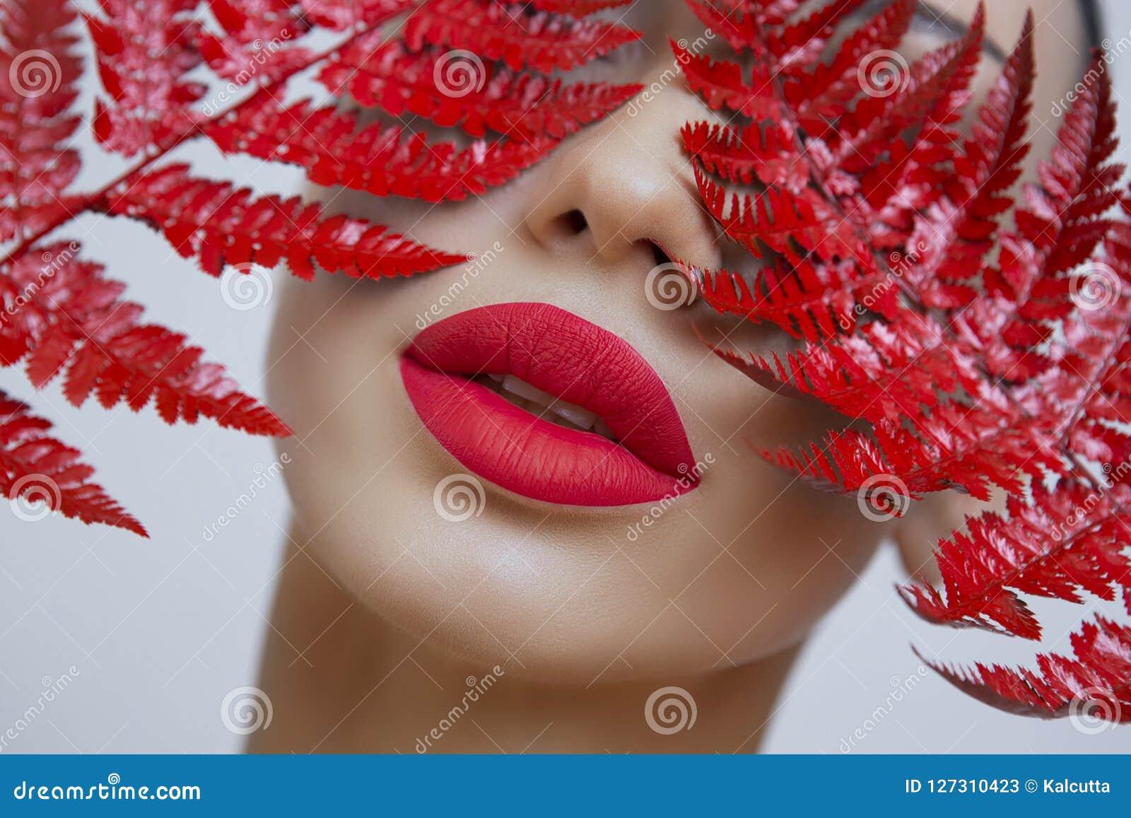 Una donna con le labbra opache rosse sensuali e una felce rivestono
