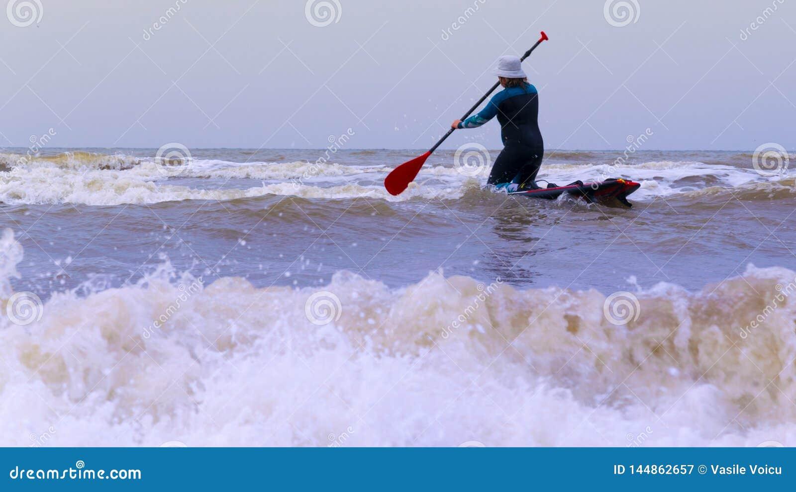 Una donna con un cappuccio sulla testa, sulla pagaia di pratica del supporto su, sul Mare del Nord nei Paesi Bassi con le grandi