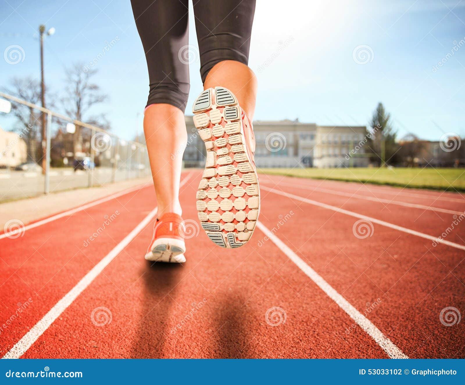 Una donna con un paio atletico delle gambe che vanno per un dur di funzionamento o di trotto