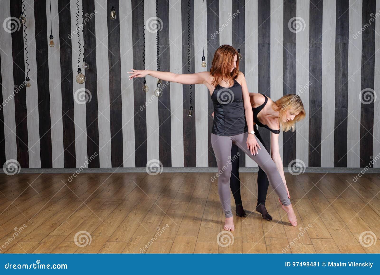 Una donna di due sport Istruttore di forma fisica Lezione con un istruttore Due donne che fanno l allungamento di nuovo all aiuto