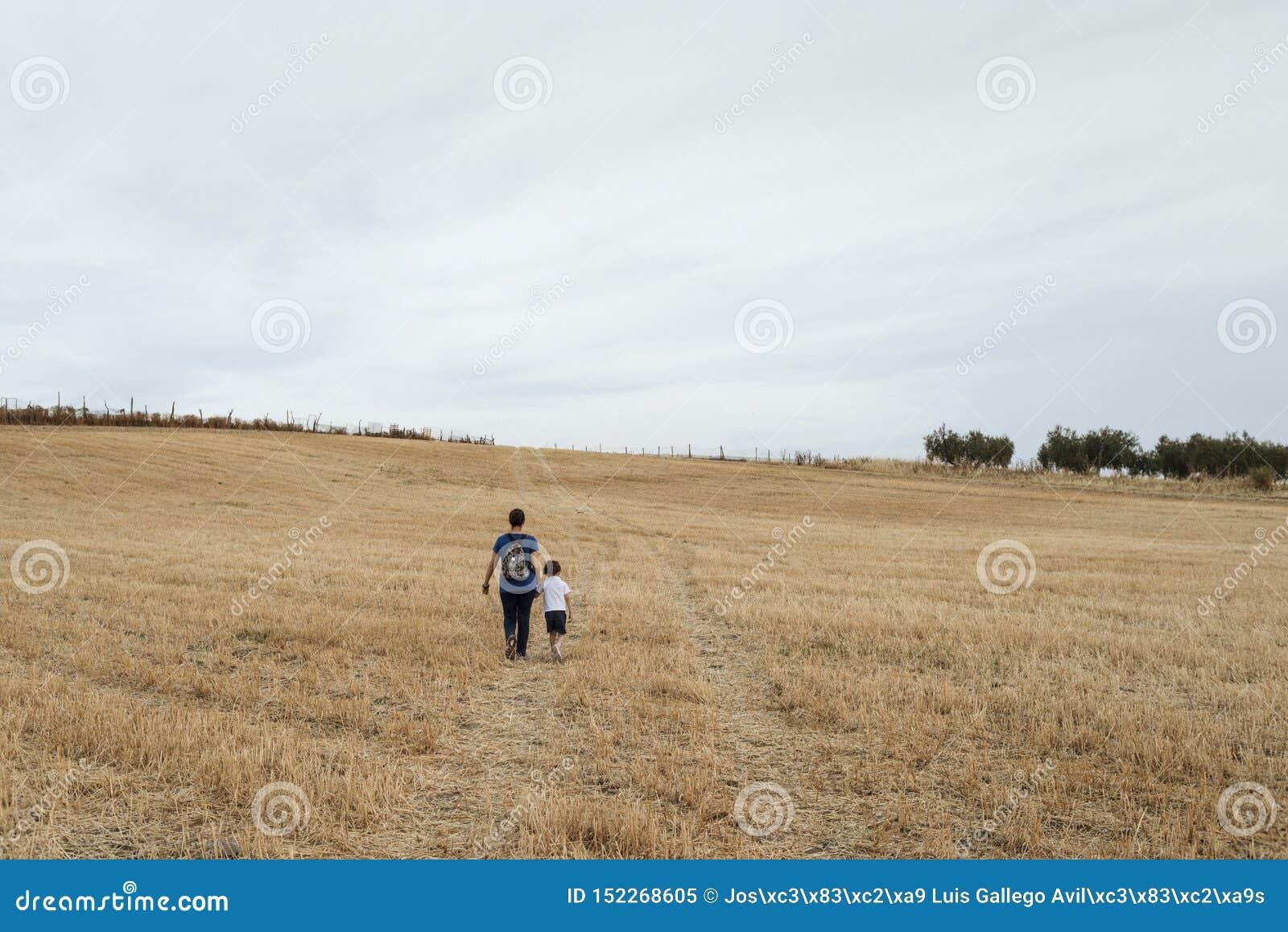 Una donna e un ragazzo che camminano attraverso un campo di grano falciato