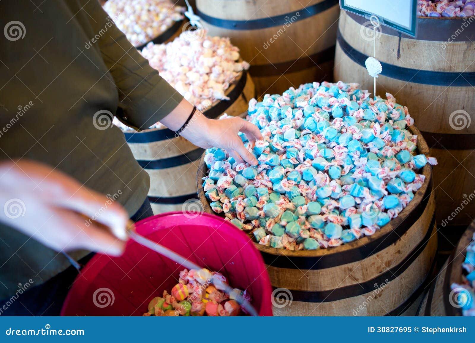 Una donna raggiunge per il taffy blu dell acqua salata in un deposito
