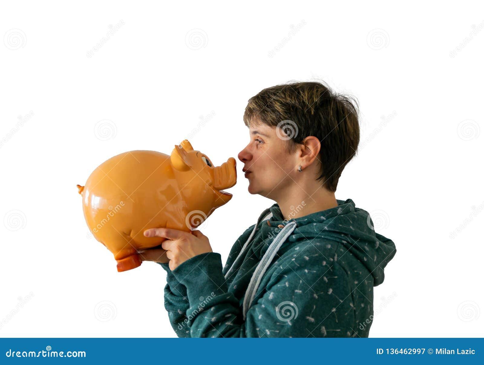 Una donna sta baciando un porcellino salvadanaio