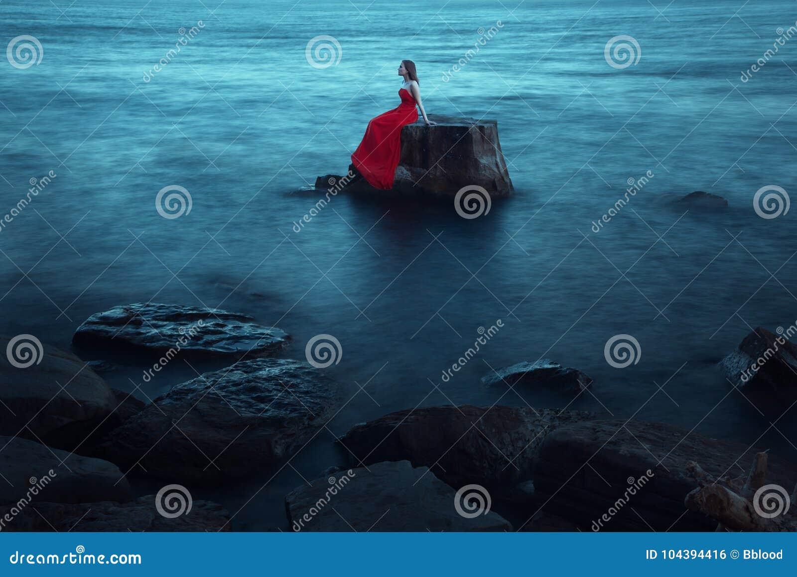 Una donna triste vicino al mare nella sera