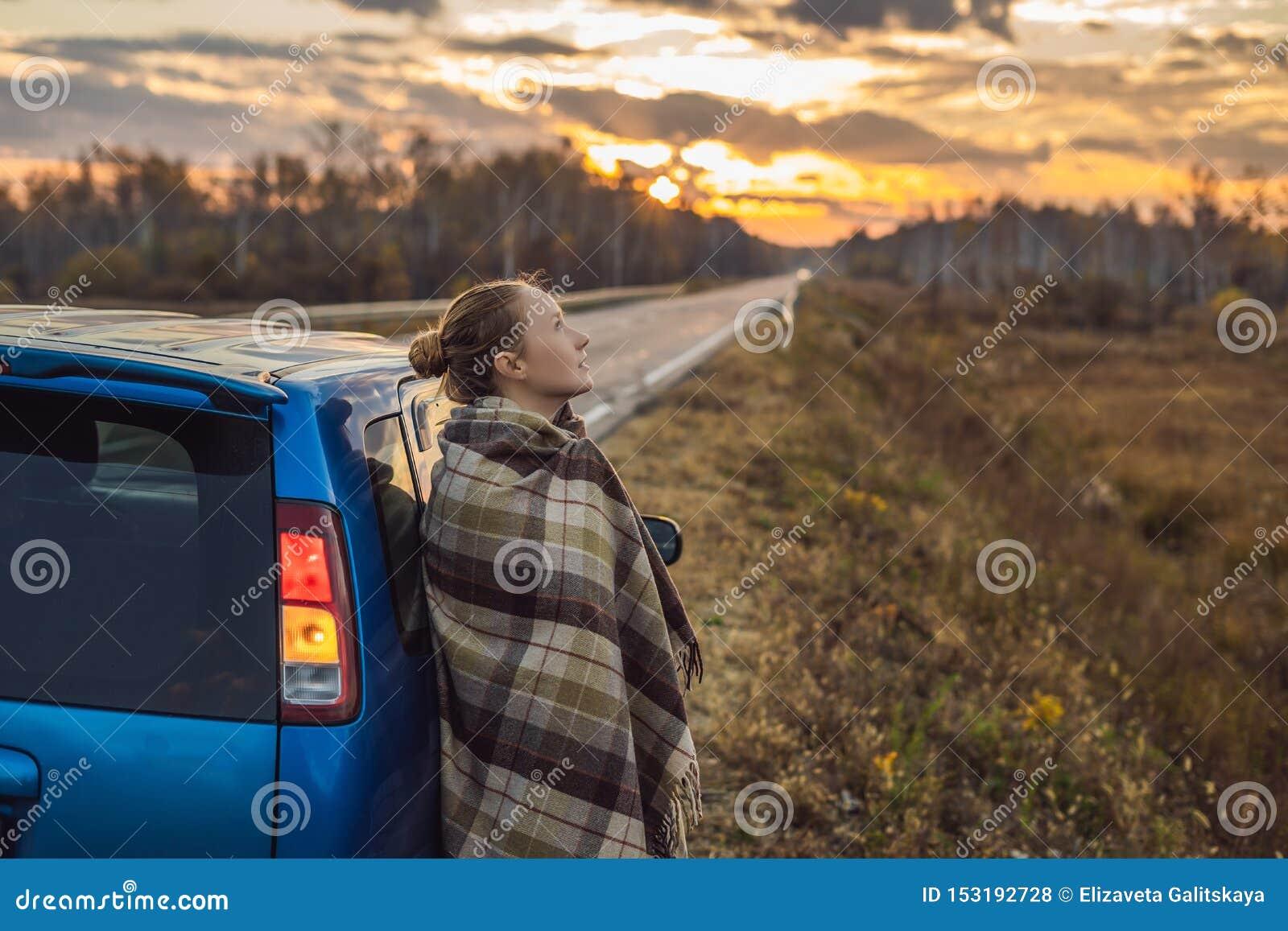 Una donna in un plaid fa una pausa l automobile dal lato della strada nei precedenti dell alba Concetto di viaggio stradale