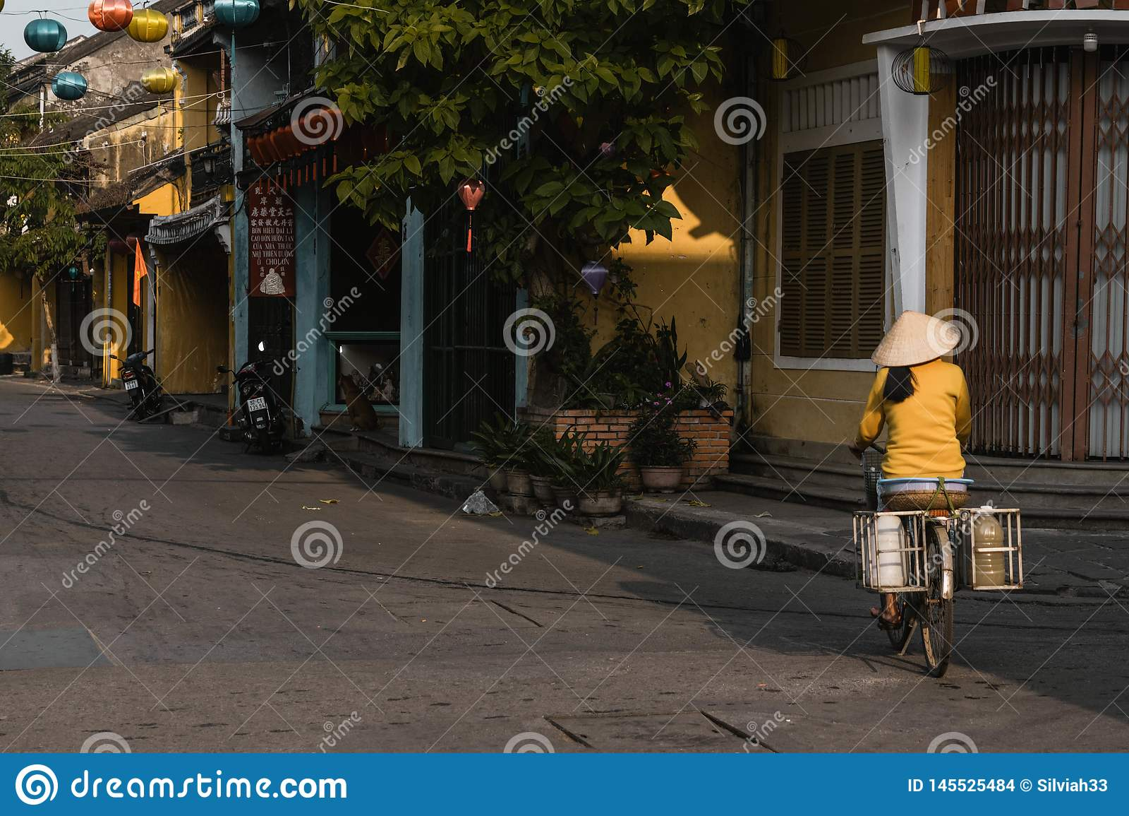 Una donna vietnamita locale guida la sua bici per lavorare in hoi