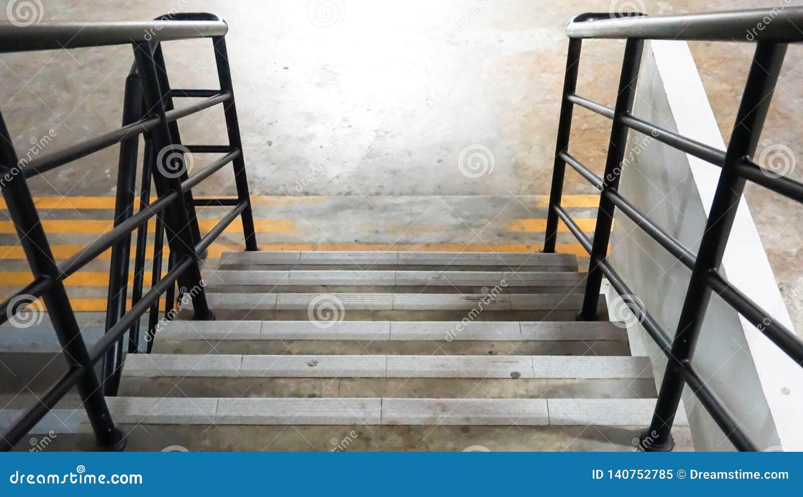 Una escalera del plumón con la cerca negra del metal