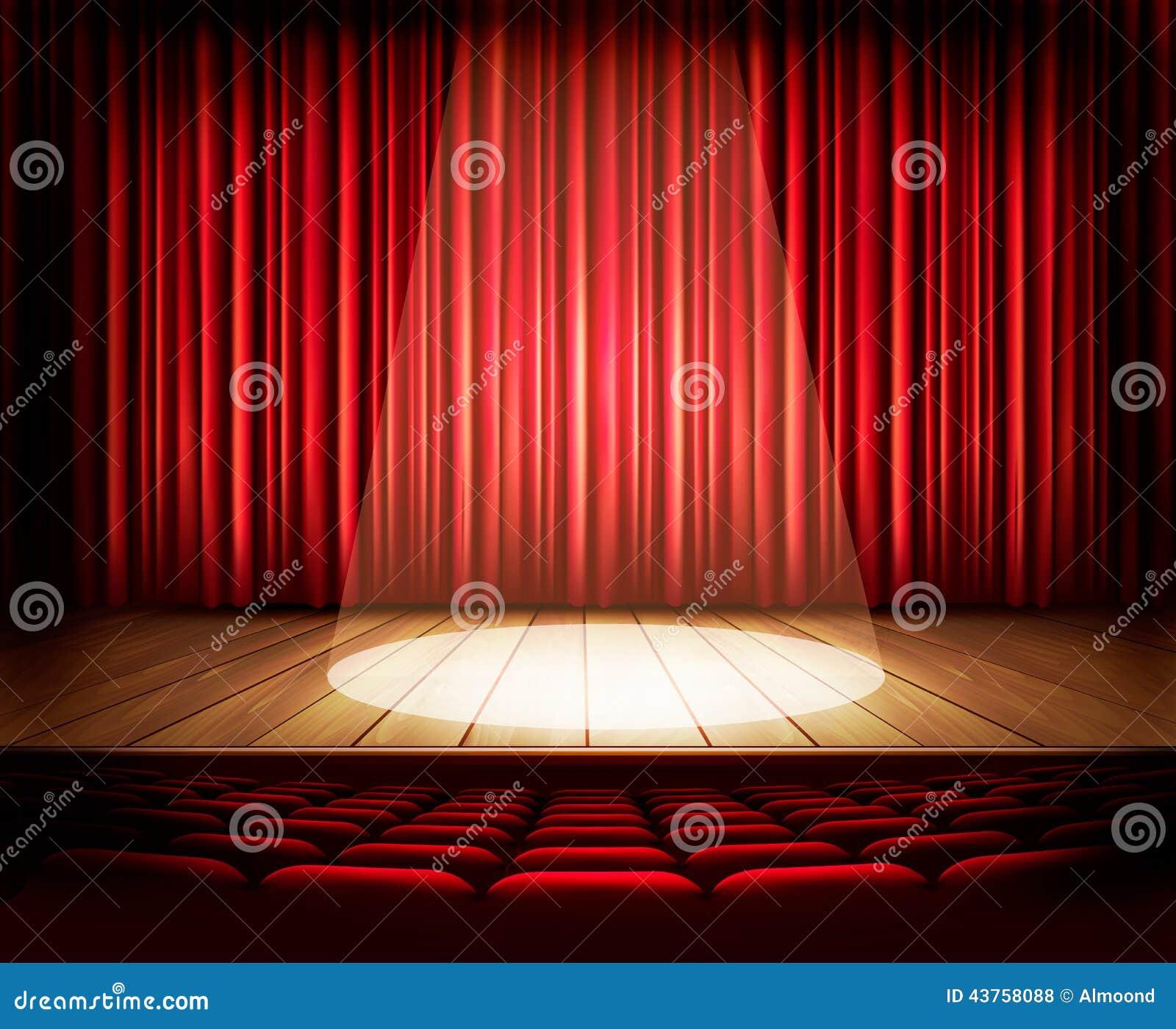 Una etapa del teatro con una cortina roja, asientos y un proyector