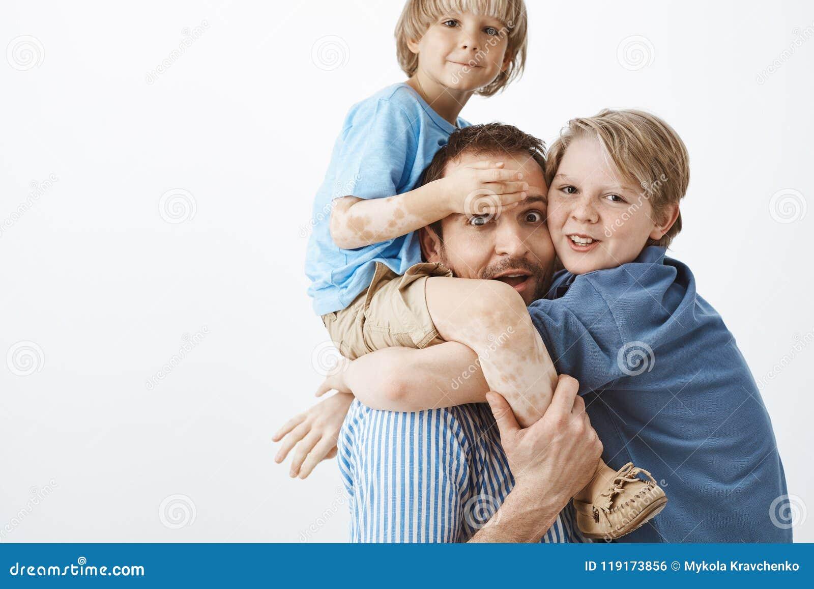 3ccaaf878b4e0 Una famiglia felice di due figli e del padre che guardano fisso e che  sorridono alla