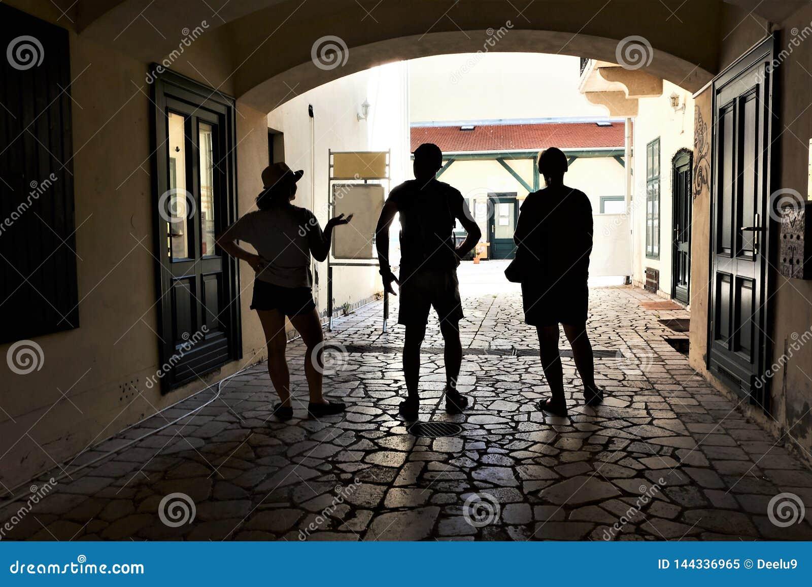Una familia de tres viajeros que buscan la sombra en un pasillo en una ciudad histórica de Eger, Hungría