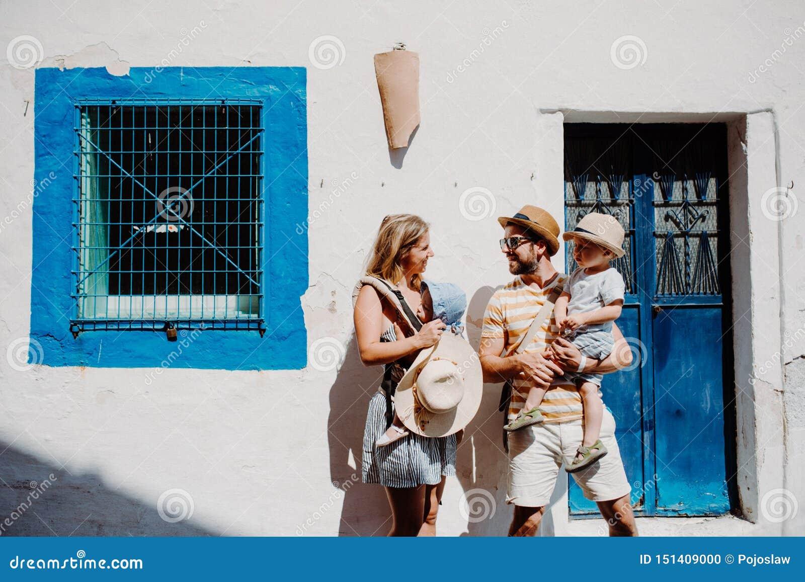 Una familia joven con dos niños del niño que se colocan en ciudad el vacaciones de verano