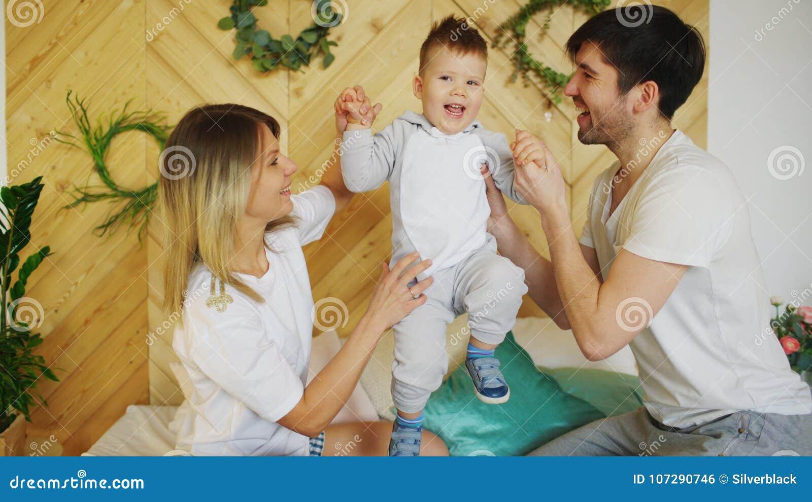 Una Familia Joven Con El Pequeno Juego Del Hijo En Cama En El