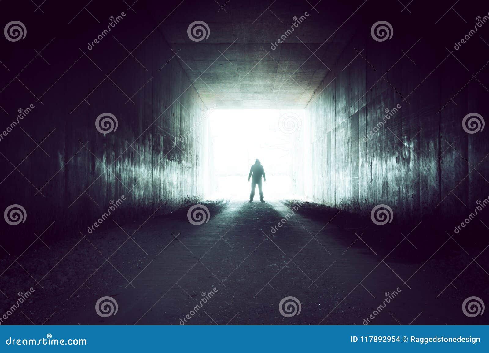 Una figura silueteada encapuchada que se coloca al borde de un túnel que mira hacia fuera sobre una luz sobreexpuesta brillante