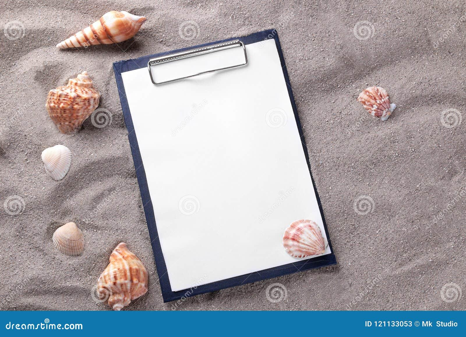 Una forma en blanco para registrar en la arena del mar con diversas cáscaras