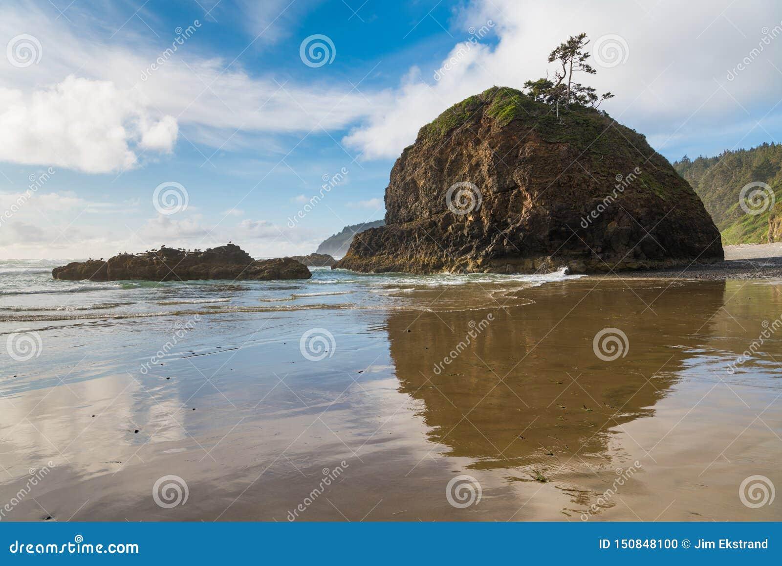 Una formación de roca de la pila del mar y un cielo azul hermoso con las nubes blancas que remolinan reflejadas sobre la arena mo
