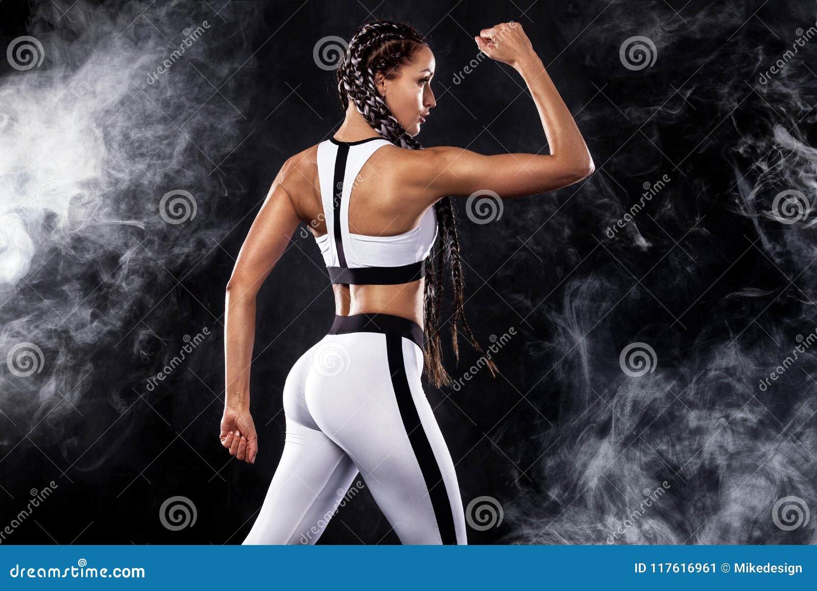 Una forte donna atletica su fondo nero che dura nella motivazione bianca degli abiti sportivi, di forma fisica e di sport Concett