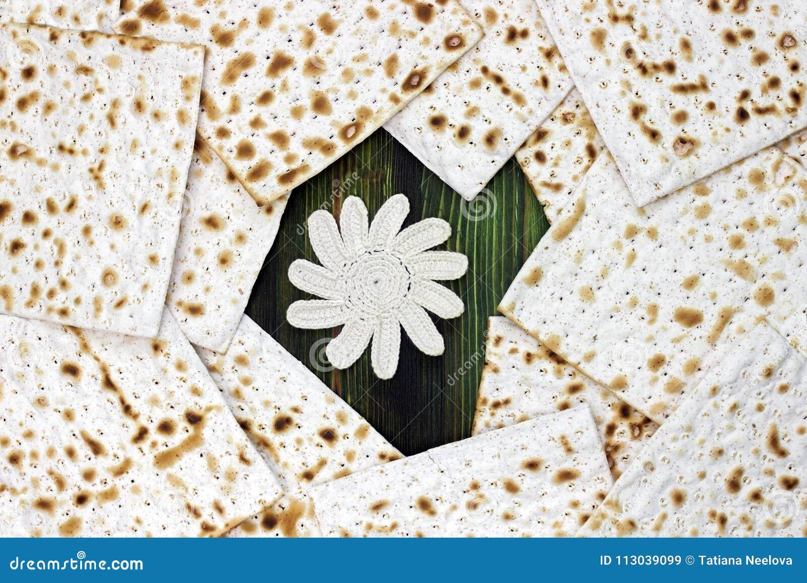 Una foto de los pedazos del matzah y el ganchillo florecen en la tabla de madera Matzah para los días de fiesta judíos de la pasc