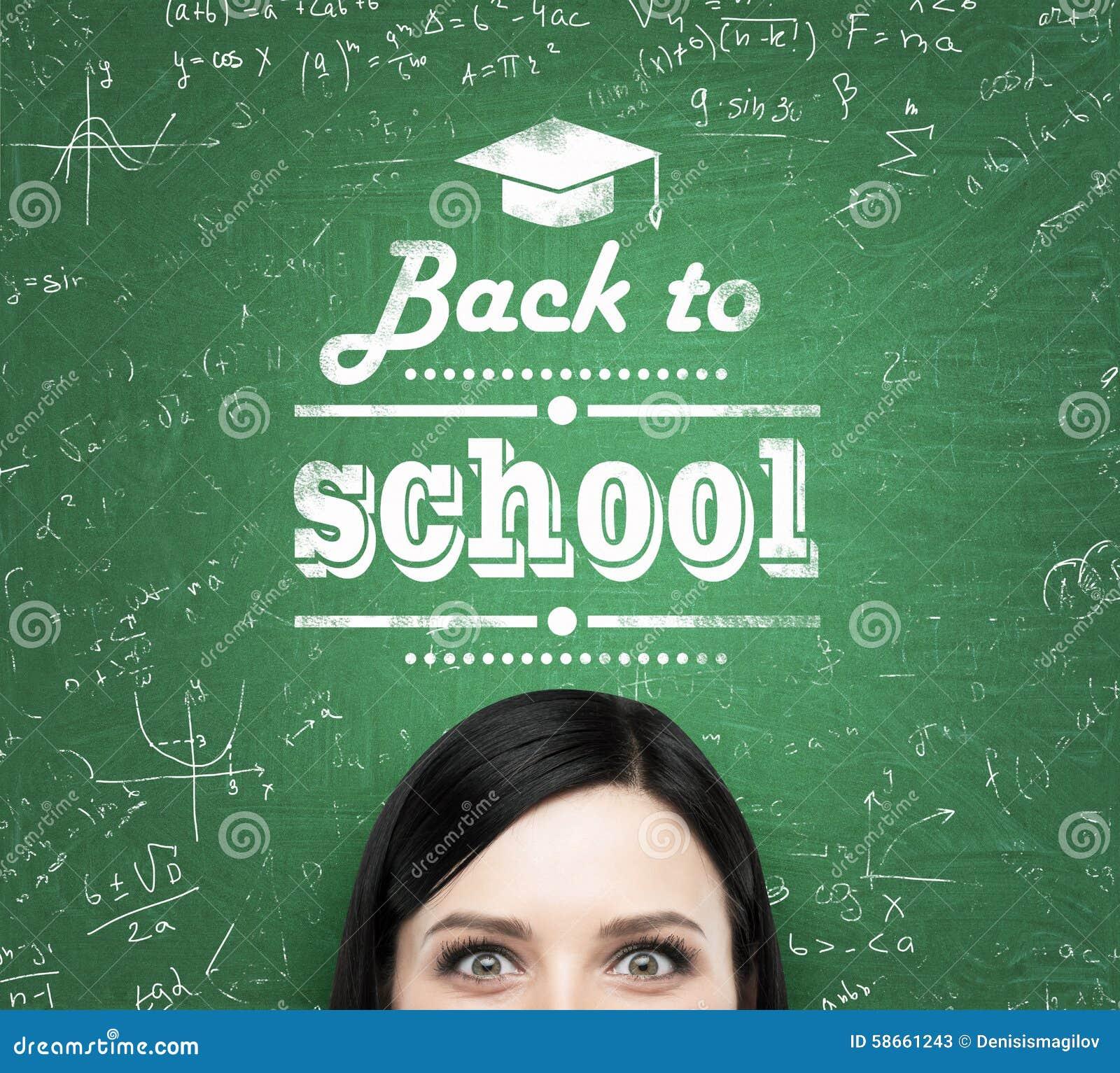 Una frente de la muchacha y de las palabras:  de nuevo a escuela  que se escriben en la pizarra verde