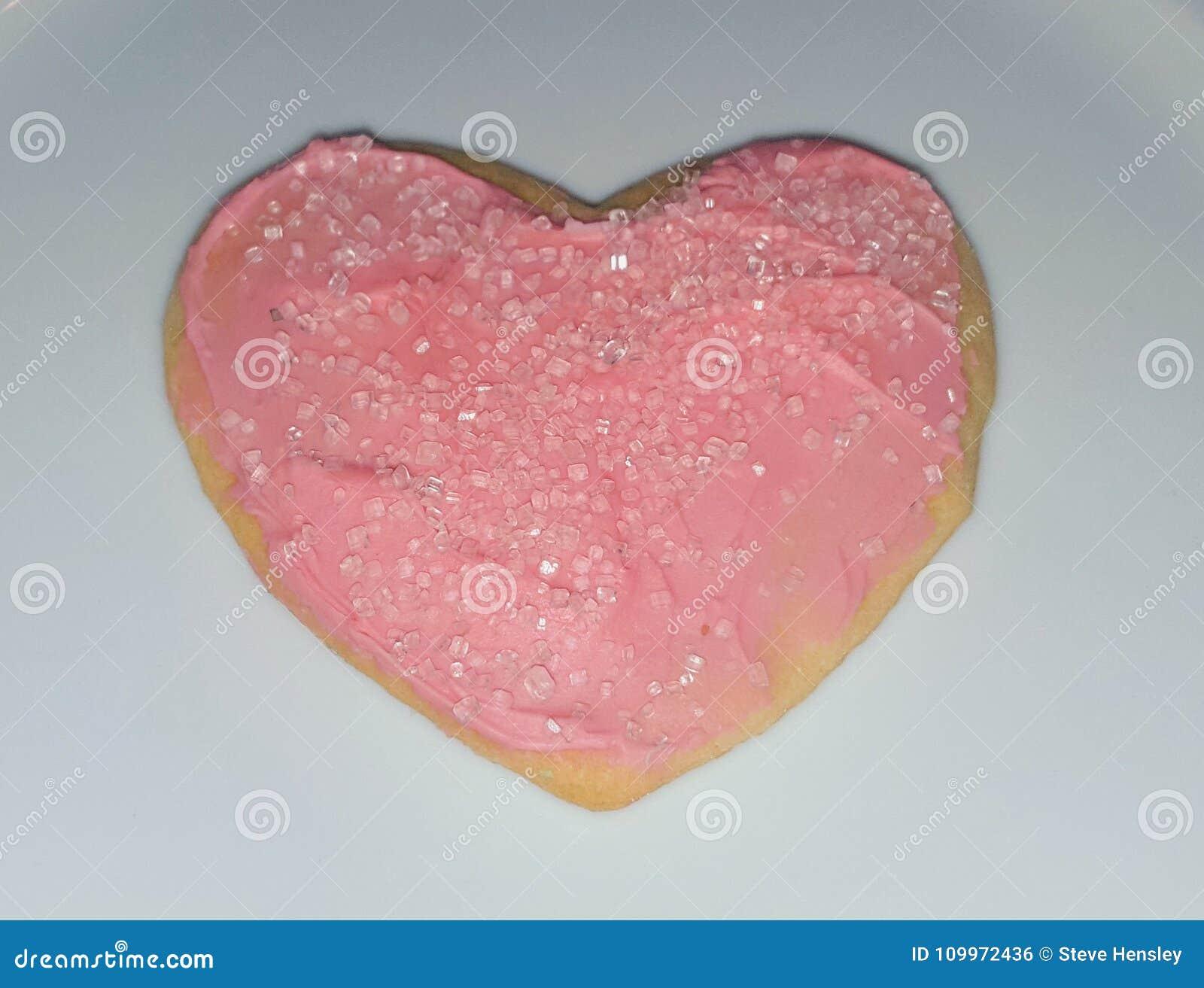 Una galleta de azúcar en forma de corazón con la formación de hielo rosada y el rosa asperja para Valentine& x27; día de s