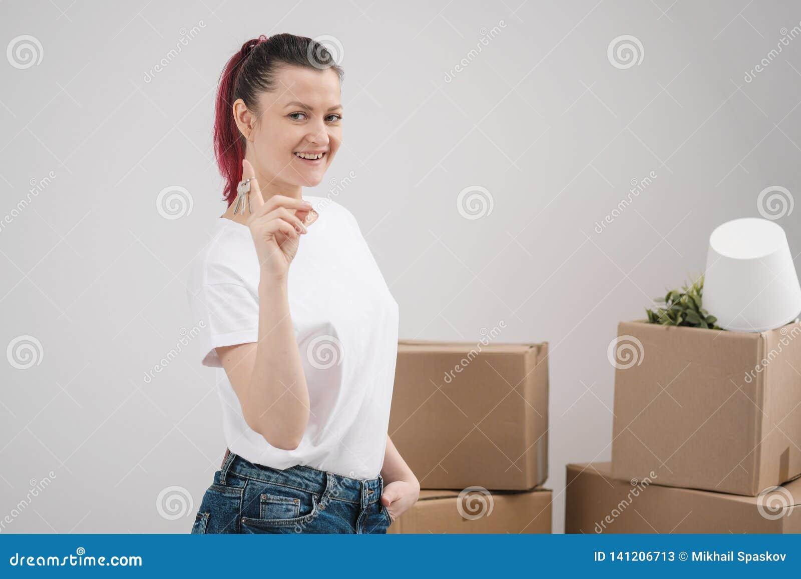 Una giovane bella ragazza castana in una maglietta bianca tiene in sue mani le chiavi ad una nuova casa, contro lo sfondo di