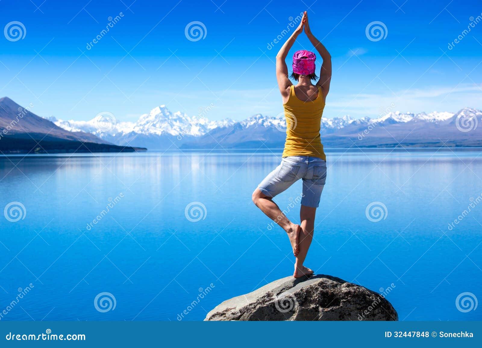 Una giovane donna attraente che fa una posa di yoga per equilibrio e che allunga vicino al lago
