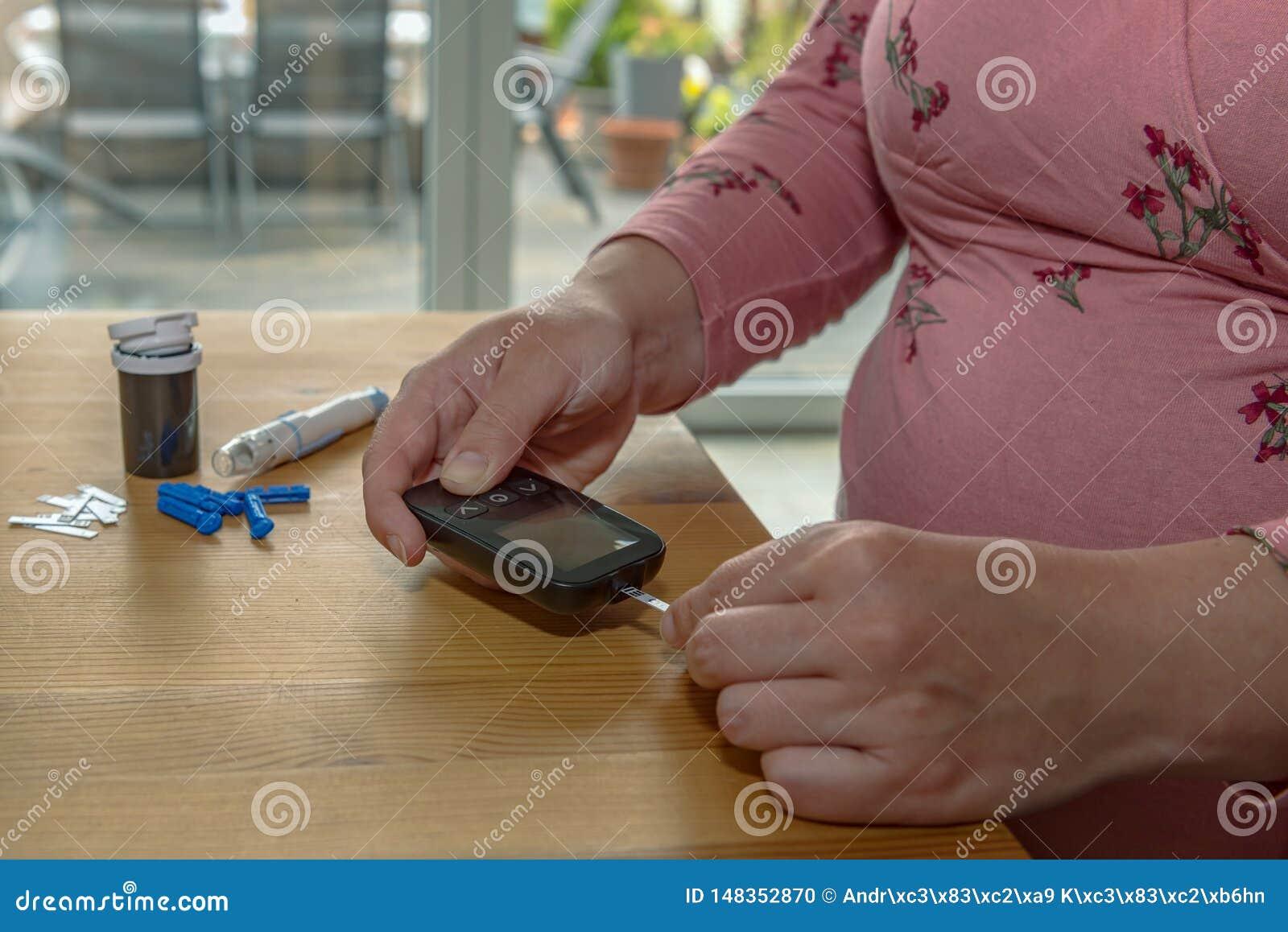 Una giovane donna a casa controlla il suo sangue