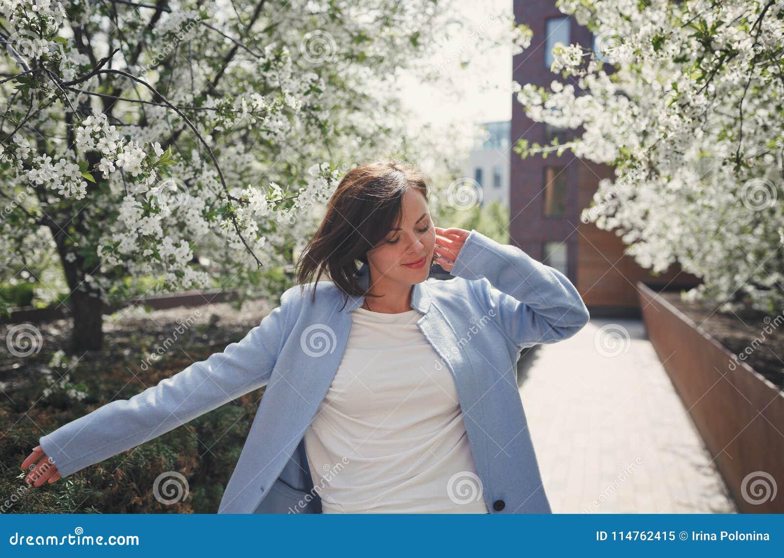 Una giovane donna castana sorridente graziosa con i capelli di scarsità in un cappotto blu dell estate balla in un parco sboccian