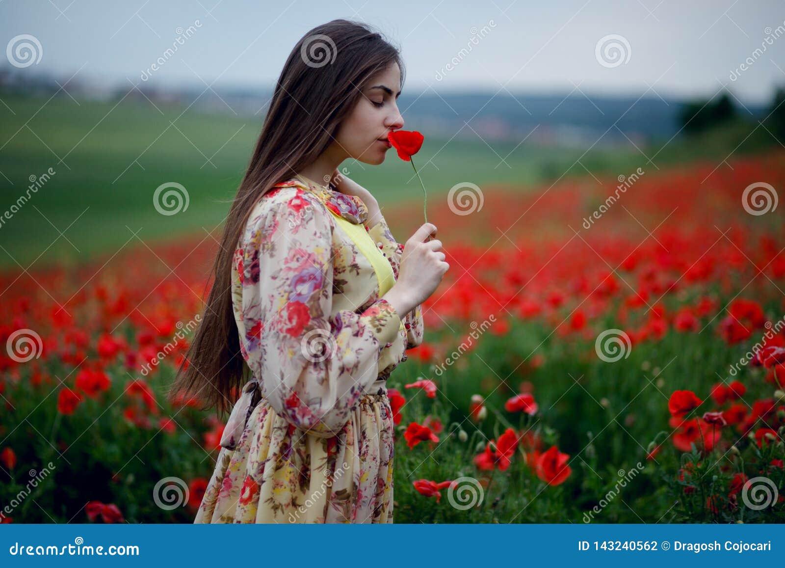 Una giovane donna con capelli lunghi che durano in vestito, stante nel giacimento di fiori dei papaveri, odora il papavero, fondo