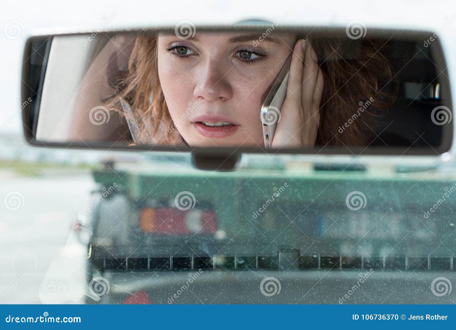 Una giovane donna determina un automobile ed i colloqui sul telefono