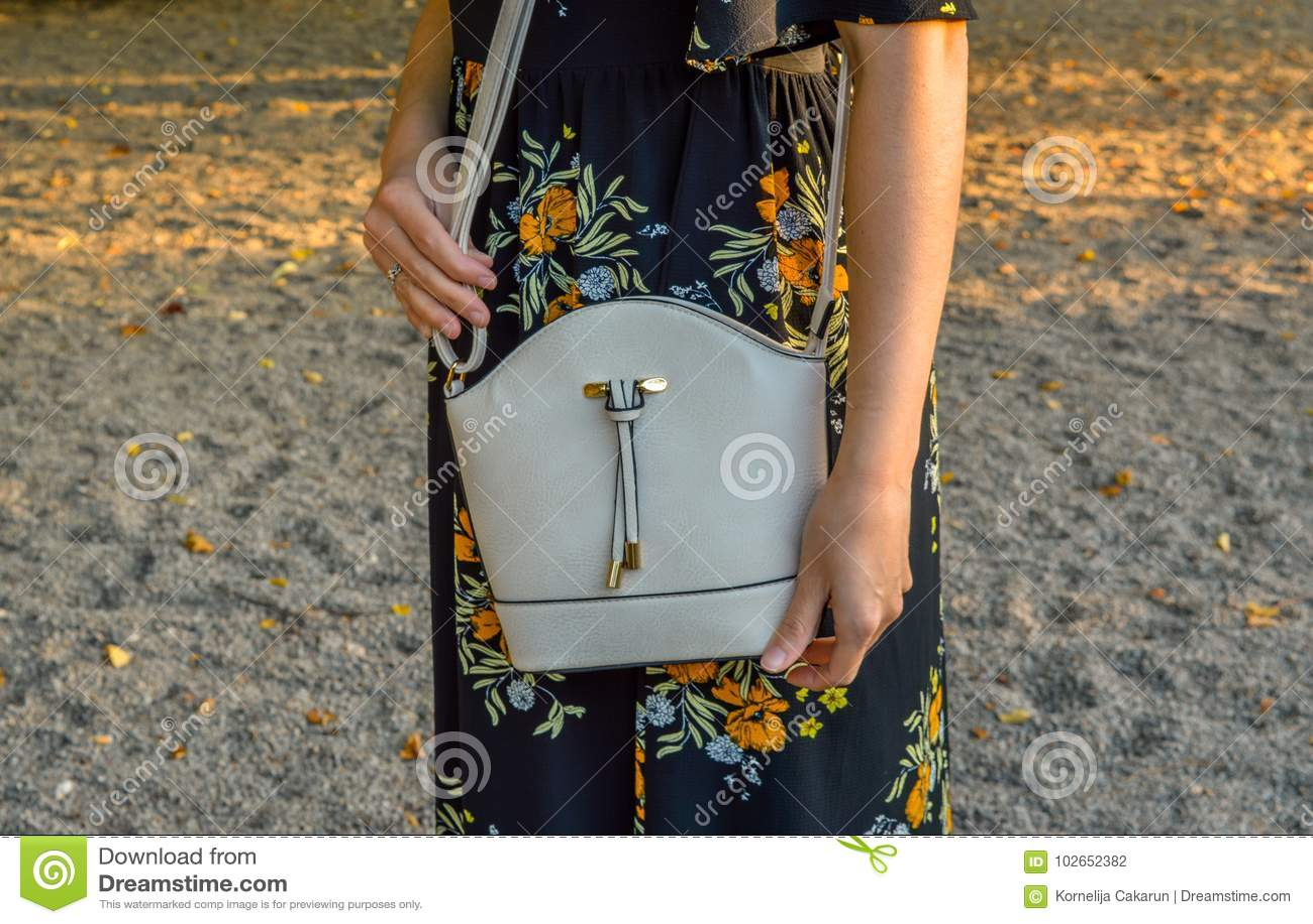 Una giovane donna, portando un vestito floreale, tenente una mini borsa