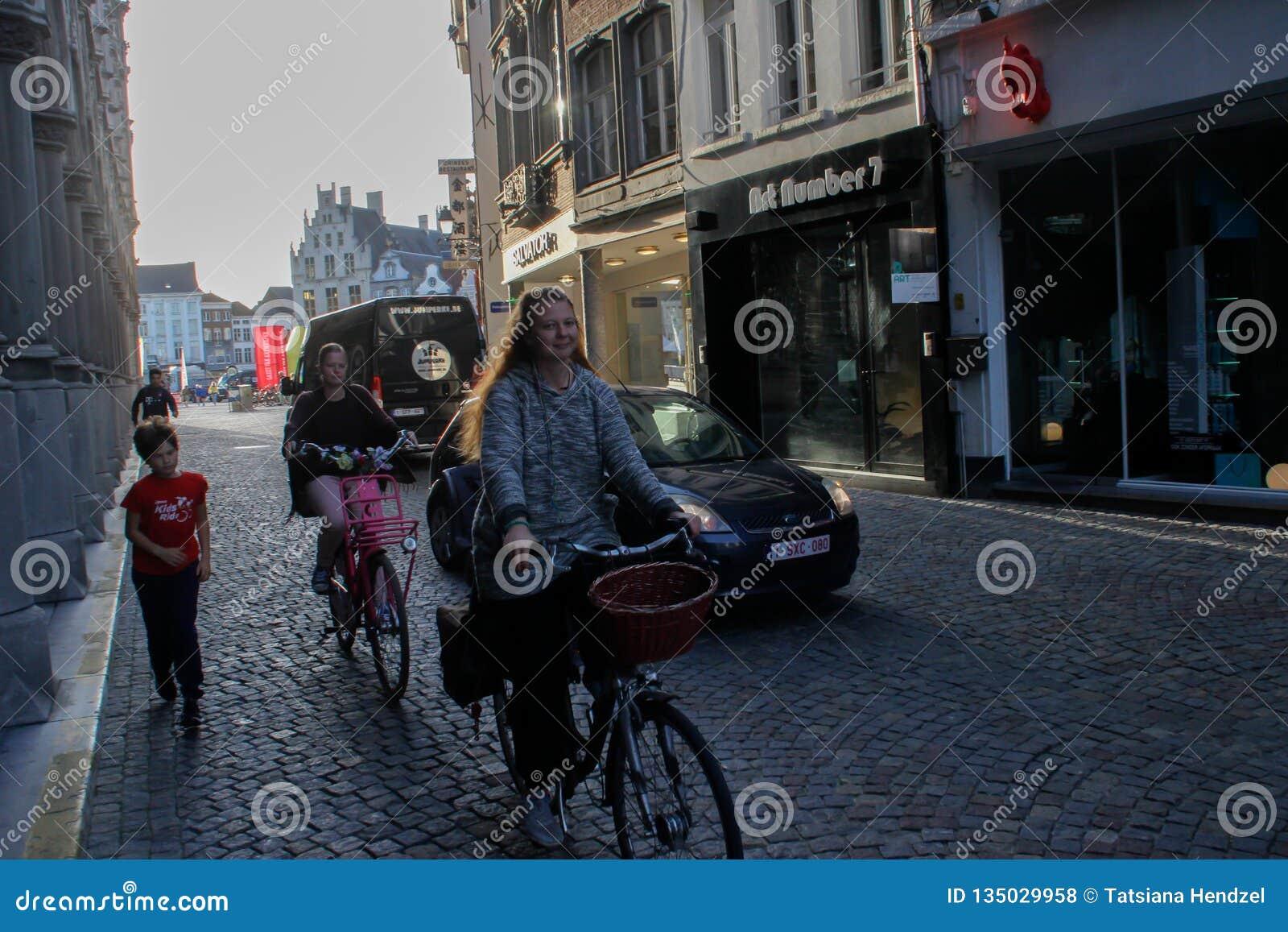 Una giovane donna sorridente felice con capelli rossi guida una bicicletta giù la via per comperare