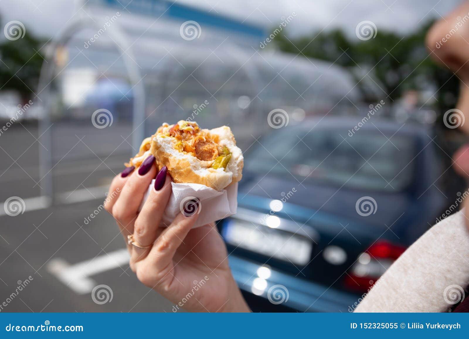 Una giovane donna tiene un hot dog pungente