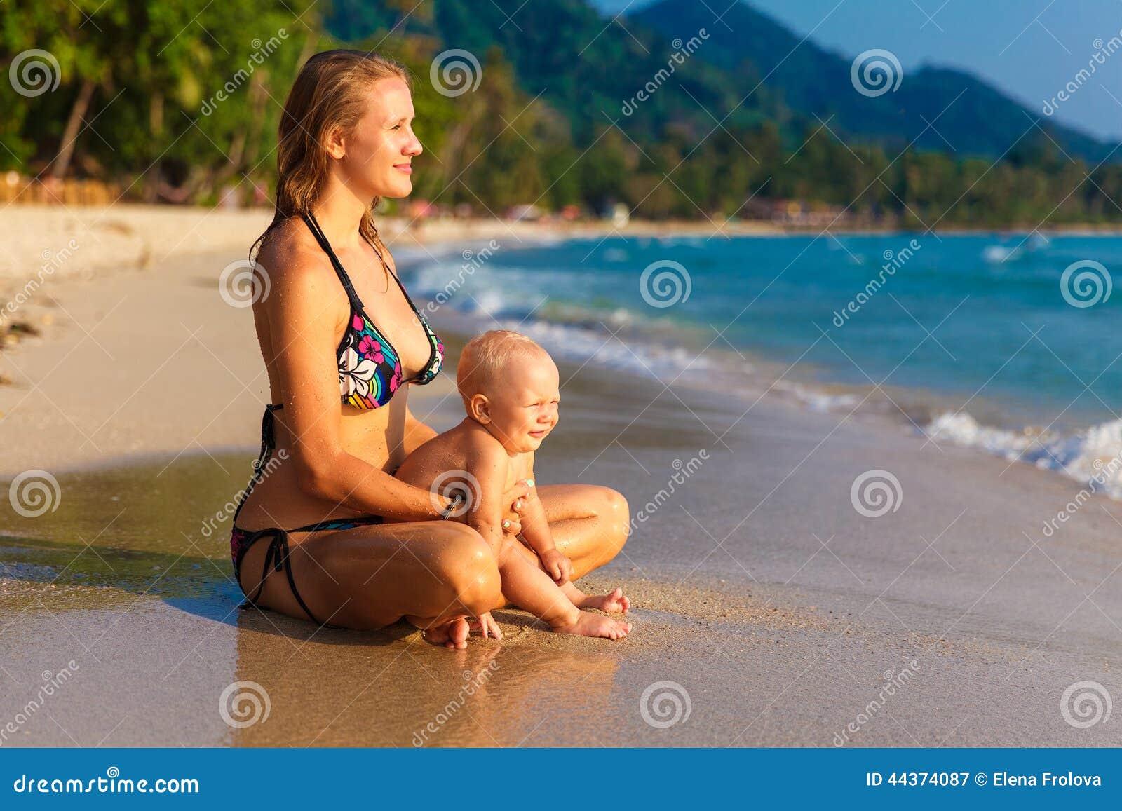 Una giovane madre con un bambino divertendosi su una spiaggia tropicale nazioni