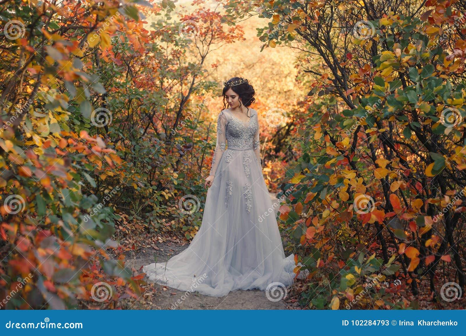 Una giovane principessa cammina in natura dorata di autunno