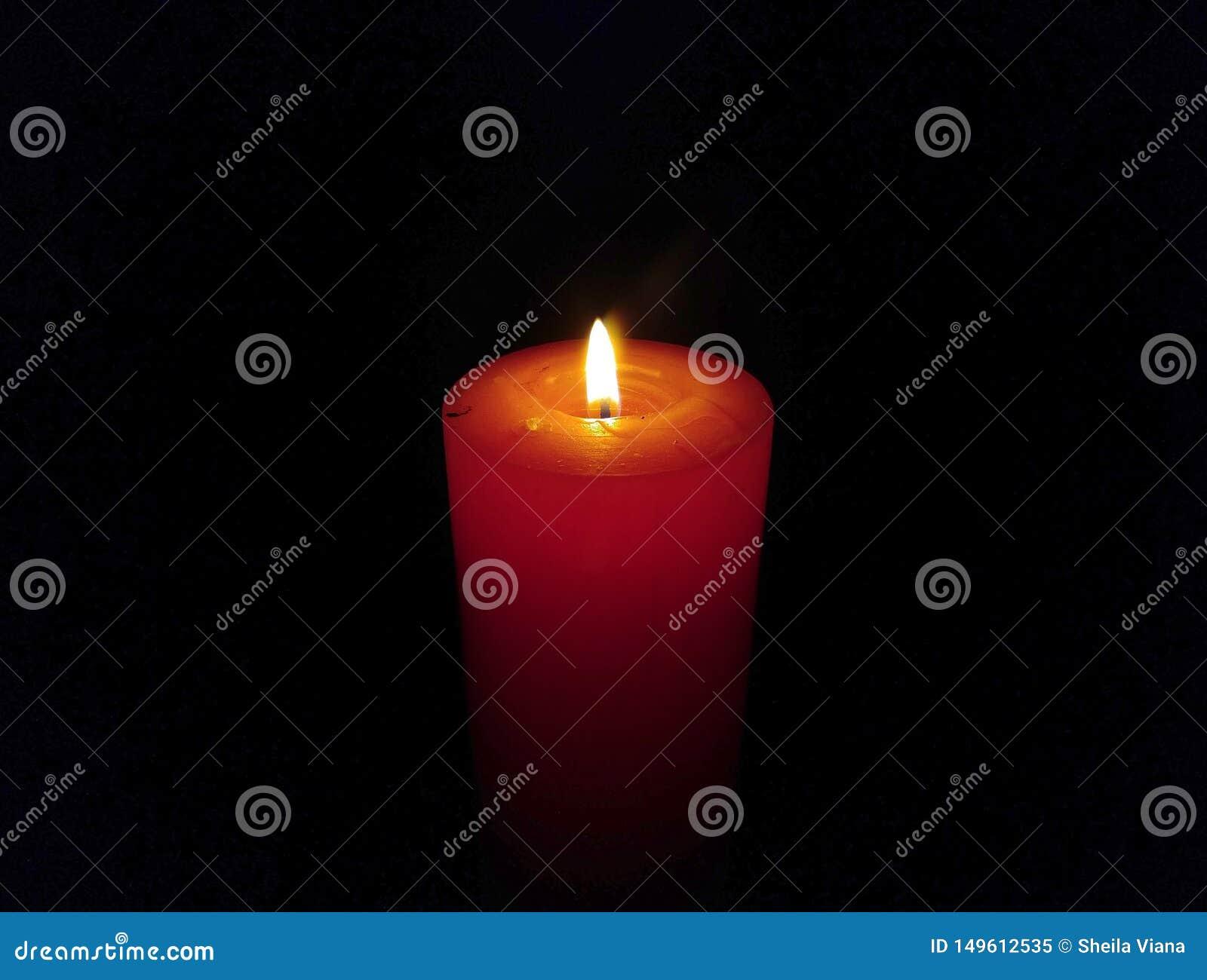 Una grande combustione della candela della cera isolata su fondo nero