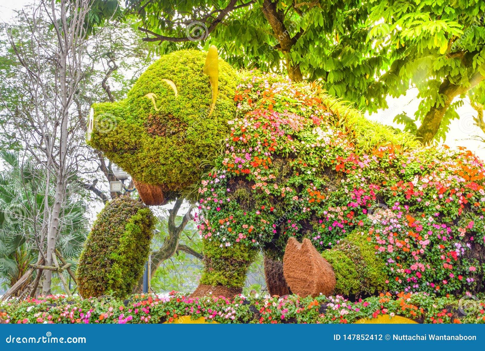 Una grande statua del maiale di sorriso e di seduta decorata con i bei fiori ed i fiori variopinti in un parco a Hanoi, Vietnam