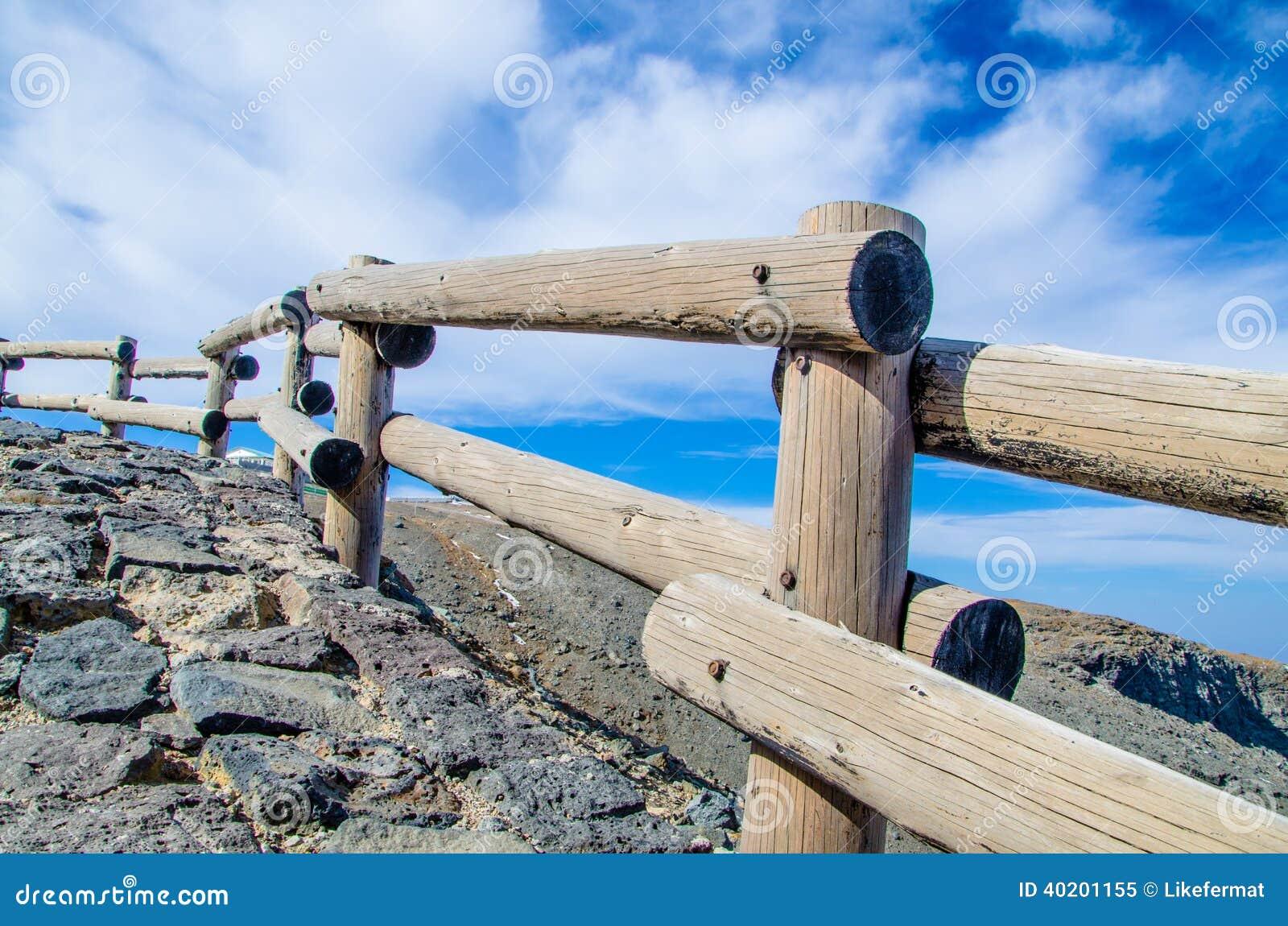 Una guardavia di legno su un bordo della strada rurale con una prospettiva piacevole.