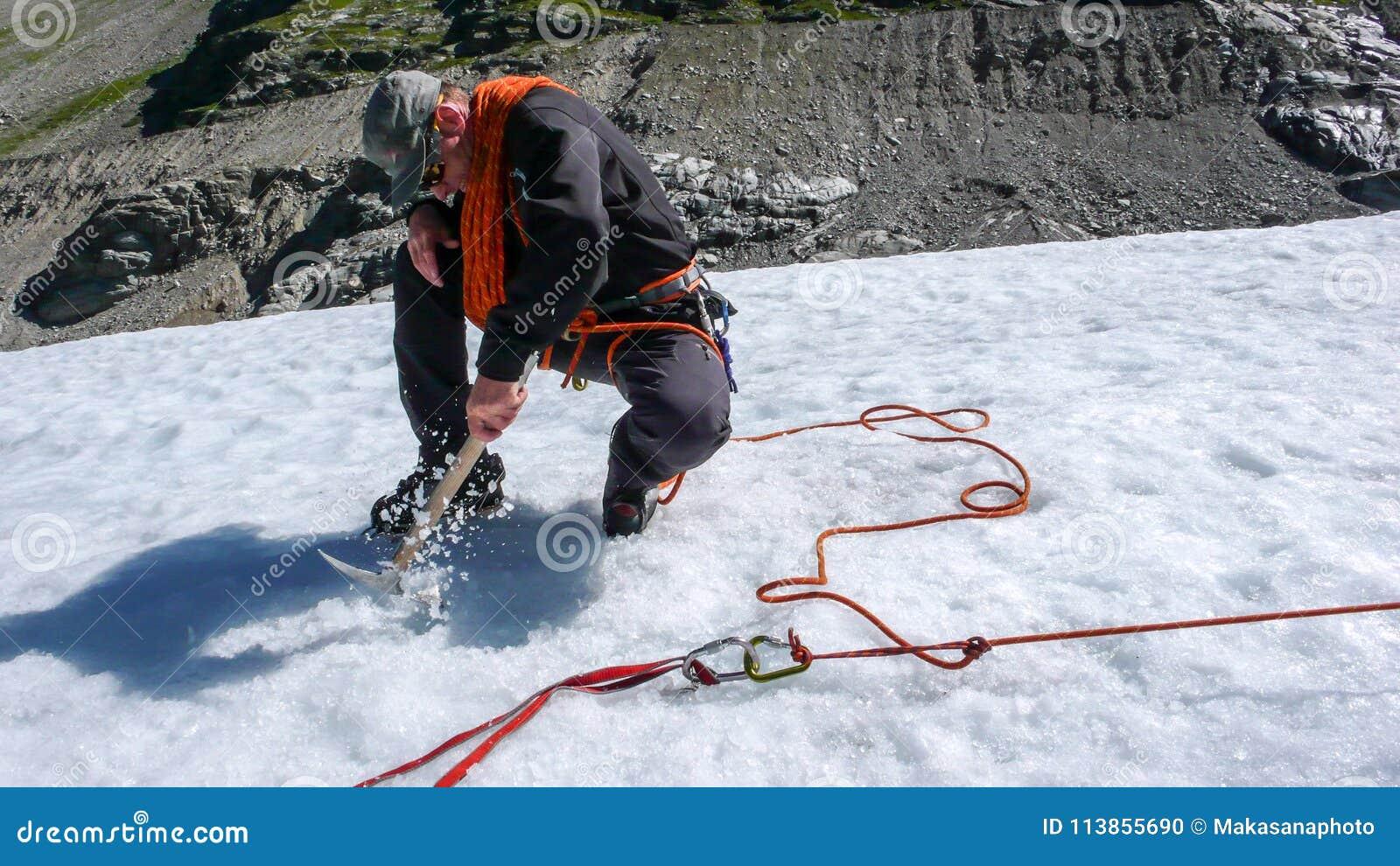 Una guida maschio della montagna che installa un sistema di carrucole per il salvataggio del crepaccio su un ghiacciaio